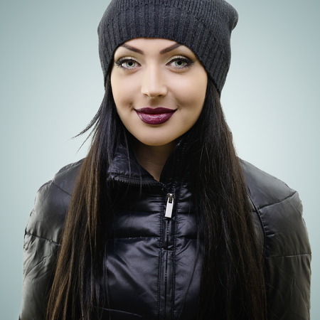 portrait of beautiful young woman in black hat and jacket, studio shot photo