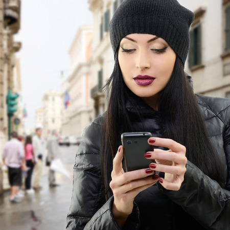 Young beautiful brunette woman touching and browsing her smart phone over city background photo