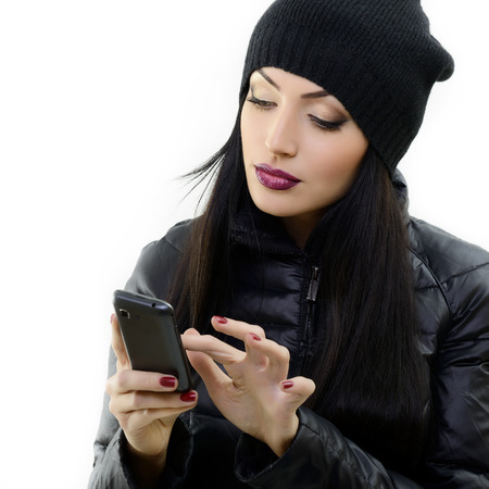 Young beautiful brunette woman touching and browsing her smart phone, over white photo
