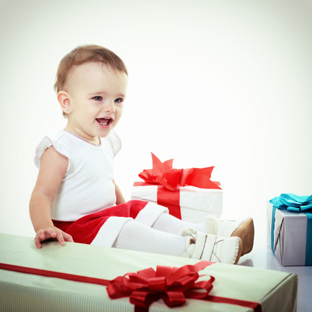 Holidays, baby girl with presents, christmas, birthday, new year, x-mas concept - happy child girl with gift boxes, toned  photo