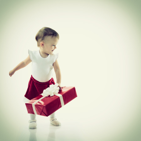 make a gift: Holidays, baby girl make a present, christmas, birthday, new year, x-mas concept - happy child girl with gift boxes