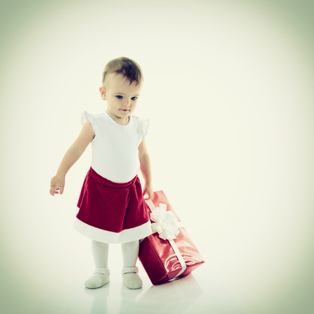 Holidays, baby girl with presents, christmas, birthday, new year, x-mas concept - happy child girl with gift boxes  photo