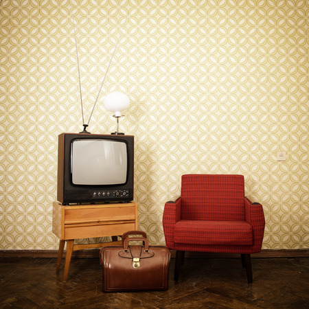 Vintage room with old fashioned armchair, retro tv, lamp and bag over oblolete wallpaper. Toned
