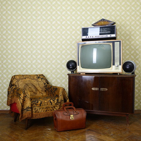 Vintage room with wallpaper, old fashioned armchair, retro tv, bag, clocks, radio player and loudspeakers photo