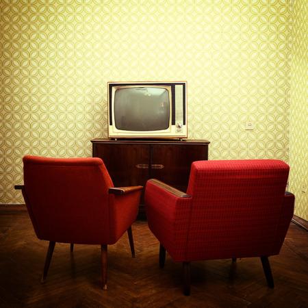 groen behang: Uitstekende kamer met twee ouderwetse fauteuils en retro TVover verouderde behang. Afgezwakt