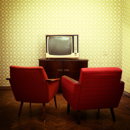 Vintage room with two old fashioned armchairs and retro tvover obsolete wallpaper. Toned photo