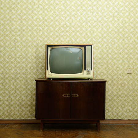 Retro tv with wooden case in room with vintage wallpaper and parquet Foto de archivo