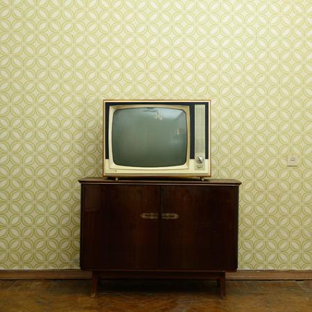 Retro TV met houten kist in de kamer met vintage behang en parket