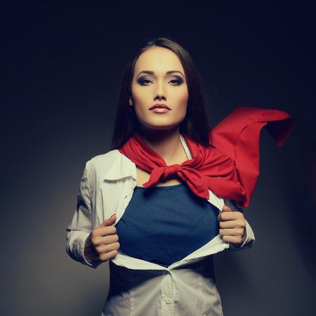 슈퍼 우먼. 슈퍼 히어로처럼 그녀의 셔츠를 여는 젊은 예쁜 여자. 톤 슈퍼 소녀 이미지. 아름다움이 세상을 저장합니다.