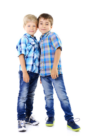 blue jeans kids: Portrait of two happy little boys friends in blue checked shirts playing together isolated on a white background