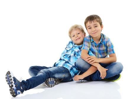 Retrato de dos chicos poco feliz amigos en cuadros azules camisas aislados en un fondo blanco Foto de archivo