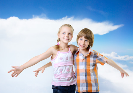 Fliers. Kids play and have fun together. Children playing fly over blue sky with clouds photo