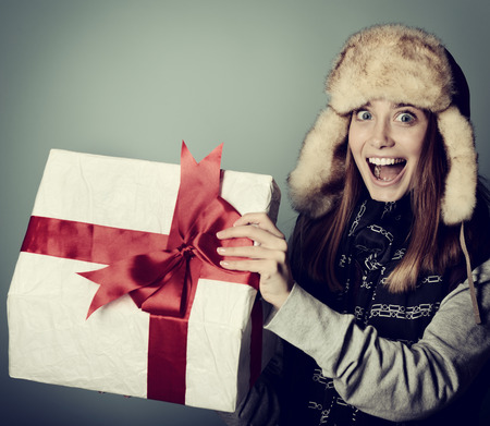 Cute excited christmas girl in winter hat opening gift box, toned photo