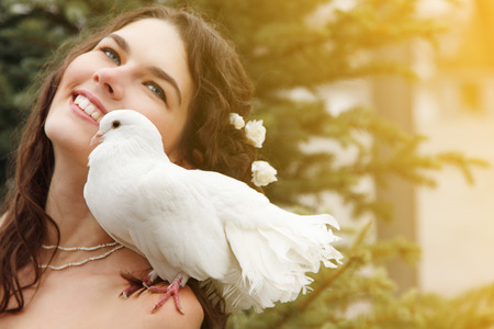 Wedding, young beautiful bride outdoor with pigeon. Toned and noise added photo