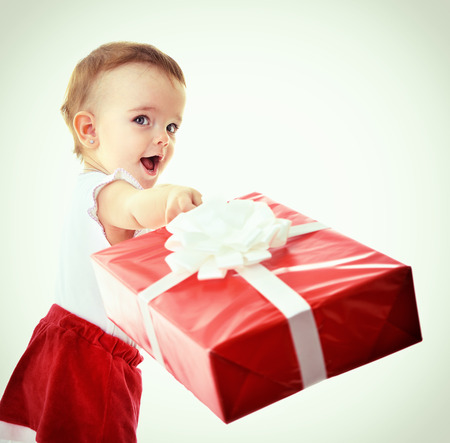 Holidays, baby girl make a present, christmas, birthday, new year, x-mas concept - happy child girl with gift boxes, toned photo