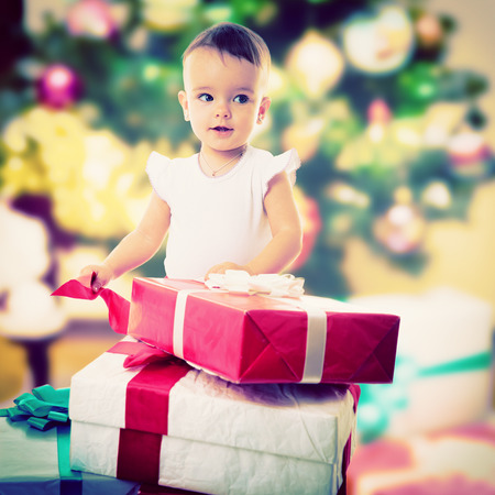 Holidays, baby girl opening box with presents, christmas, birthday, new year, x-mas concept - happy child girl with gift boxes  photo