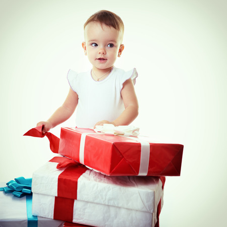 Holidays, baby girl opening box with presents, christmas, birthday, new year, x-mas concept - happy child girl with gift boxes, toned photo