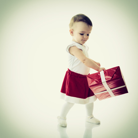 Holidays, baby girl dancing with presents, christmas, birthday, new year, x-mas concept - happy child girl with gift boxes  photo