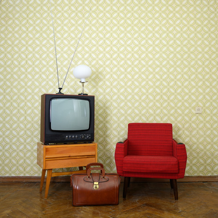 Vintage room with old fashioned armchair, retro tv, lamp and bag over oblolete wallpaper photo