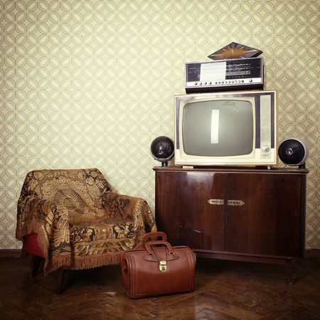 Vintage room with wallpaper, old fashioned armchair, retro tv, bag, clocks, radio player and loudspeakers. Toned photo