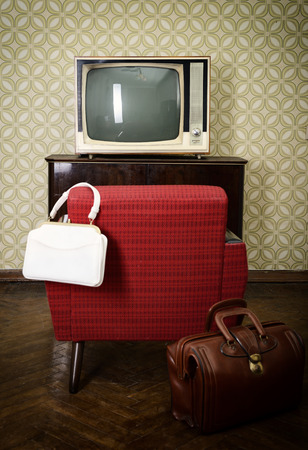 Vintage room with wallpaper, old fashioned armchair, retro tv and two bags. Toned photo