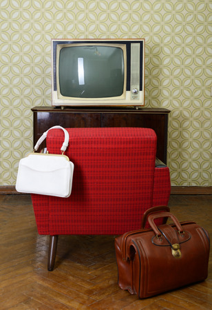 Vintage room with wallpaper, old fashioned armchair, retro tv and two bags photo