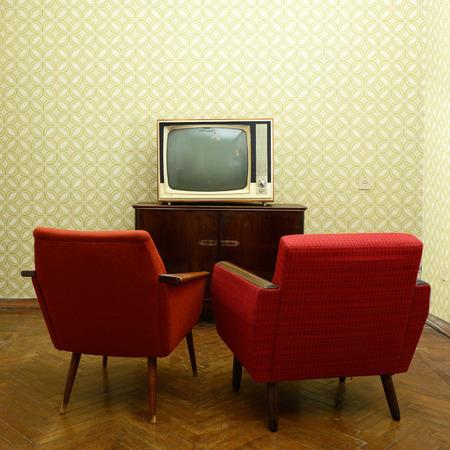 Uitstekende kamer met twee ouderwetse fauteuils en retro TVover verouderde behang