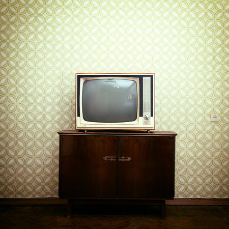 Retro tv with wooden case in room with vintage wallpaper and parquet, toned