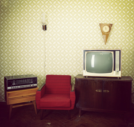 Vintage room with wallpaper, old fashioned armchair, retro tv, clocks, radio player and lamp. Toned photo