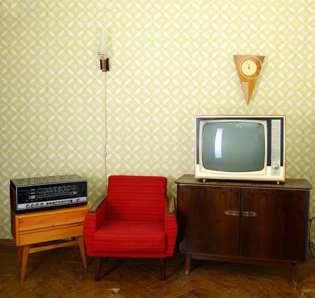 Salle vintage avec du papier peint, vieux fauteuil façonné, rétro tv, horloges, radio et lecteur de lampe