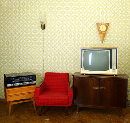 Vintage room with wallpaper, old fashioned armchair, retro tv, clocks, radio player and lamp
