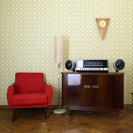 Vintage room with wallpaper, old fashioned armchair, retro player, loudspeakers, clocks and standart lamp, toned photo