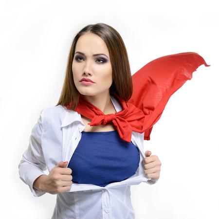 スーパーウーマン。若いかわいい女性のスーパー ヒーローのよう彼女のシャツを開いてします。白スーパー ガール。美は世界を救う 写真素材