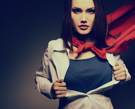 powerful: Superwoman. Young pretty woman opening her shirt like a superhero. Super girl, image toned. Beauty saves the world.