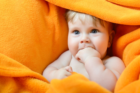 cute baby: portrait of cute baby boy lying on orange plaid and sucking his finger Stock Photo