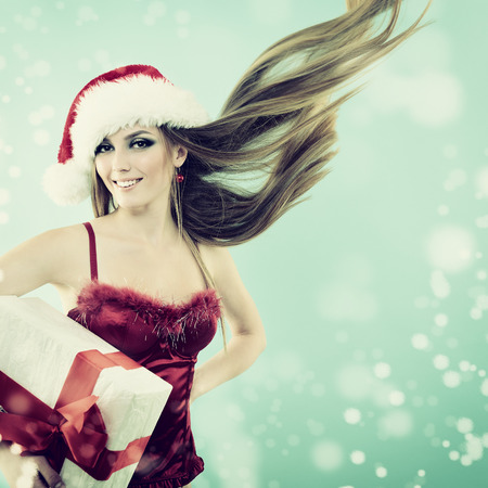 Beautiful cheerful fashion christmas girl in Santa's hat with gift box in snow, toned photo