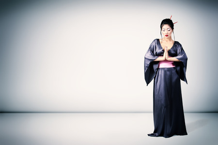 Young beautiful asian woman in kimono, full length portrait, studio shot photo