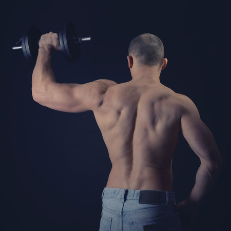 Strong athletic man with perfect body posing with dumbbells, back view, toned photo