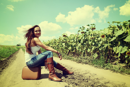 young woman with retro suitcase traveling in countryside, summer nature outdoor, toned photo