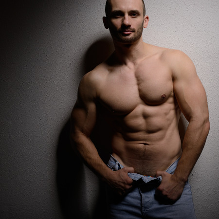 nipple man: Strong athletic man with perfect body posing in studio on black background