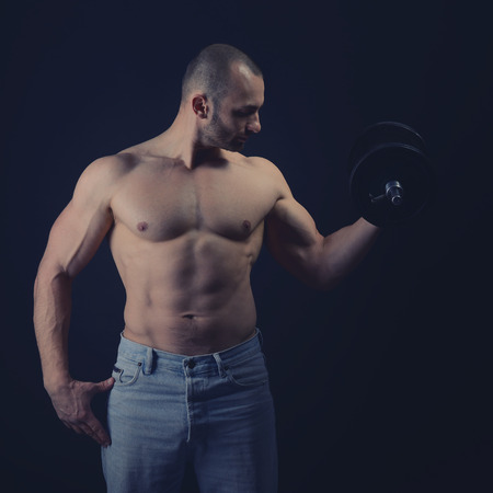 abdominal wall: Strong athletic man with perfect body posing with dumbbells