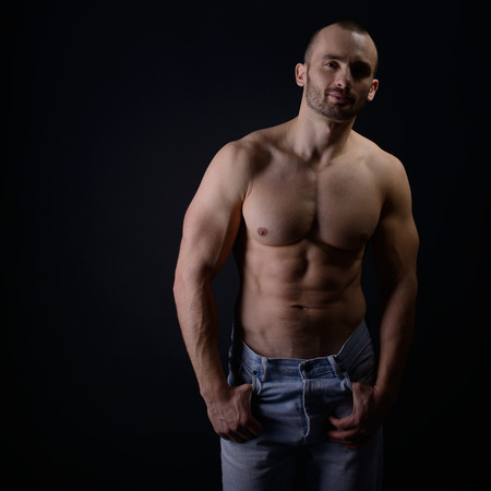 nipple man: Strong athletic man with perfect body posing in studio on black background  Stock Photo