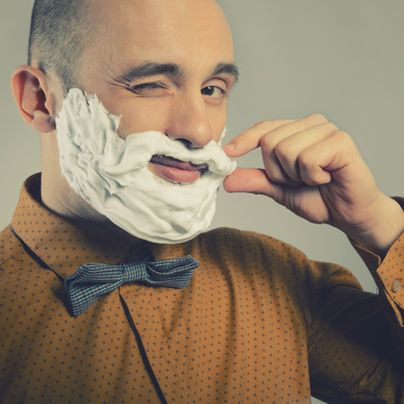forceful: Hipster. Funny portrait of trendy man making moustache and beard of shaving foam and gives wink, toned.