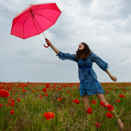 Young beautiful woman flying with wind holding red umbrella from a poppy field, summer outdoor. photo