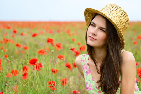 gentle dream vacation: Young beautiful calm girl in straw hat dreamomg on a poppy field, summer outdoor.