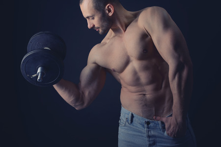 nipple man: Strong athletic man with perfect body posing with dumbbells, toned Stock Photo