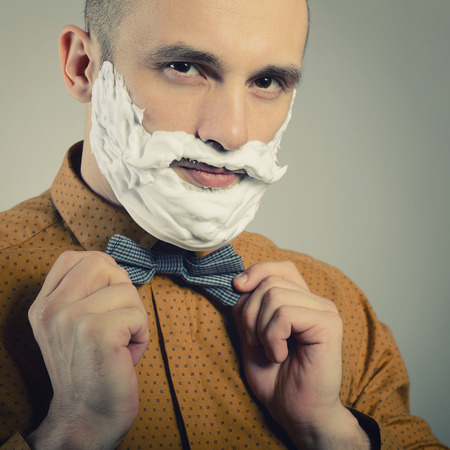 Hipster. Funny portrait of trendy man with moustache and beard of shaving foam, toned.
