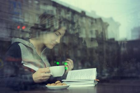 コーヒーを飲みながら本座っている都市のカフェで屋内を読む若い女性。カフェ都市生活。10 代の女の子のカジュアルな肖像画。トーンダウン。