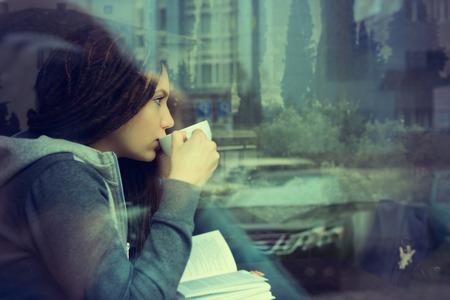 Jonge vrouw drinken koffie en het lezen boek zitten indoor in de stedelijke cafe. Cafe stad lifestyle. Casual portret van tienermeisje. Afgezwakt. Stockfoto