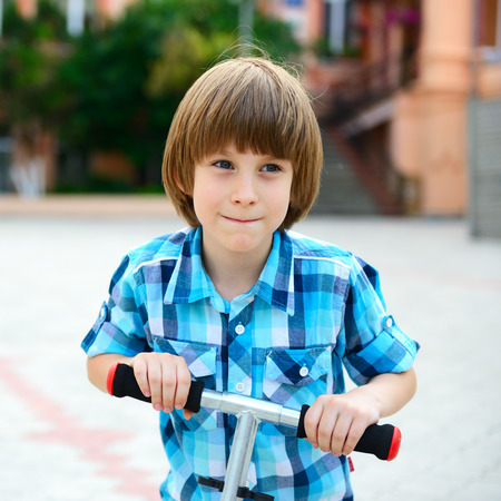 Cute boy riding two scooter photo